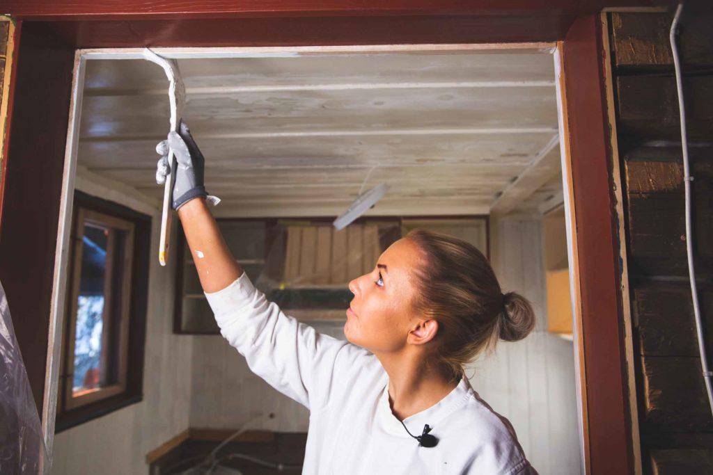 lene maler en dørkarm på hytte i trysil
