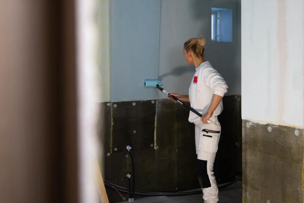 kvinnelig maler rullemaler blått på vegg