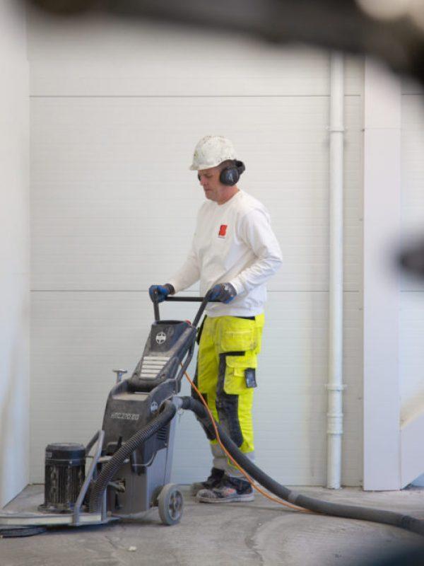 mann pusser et betonggulv innendørs